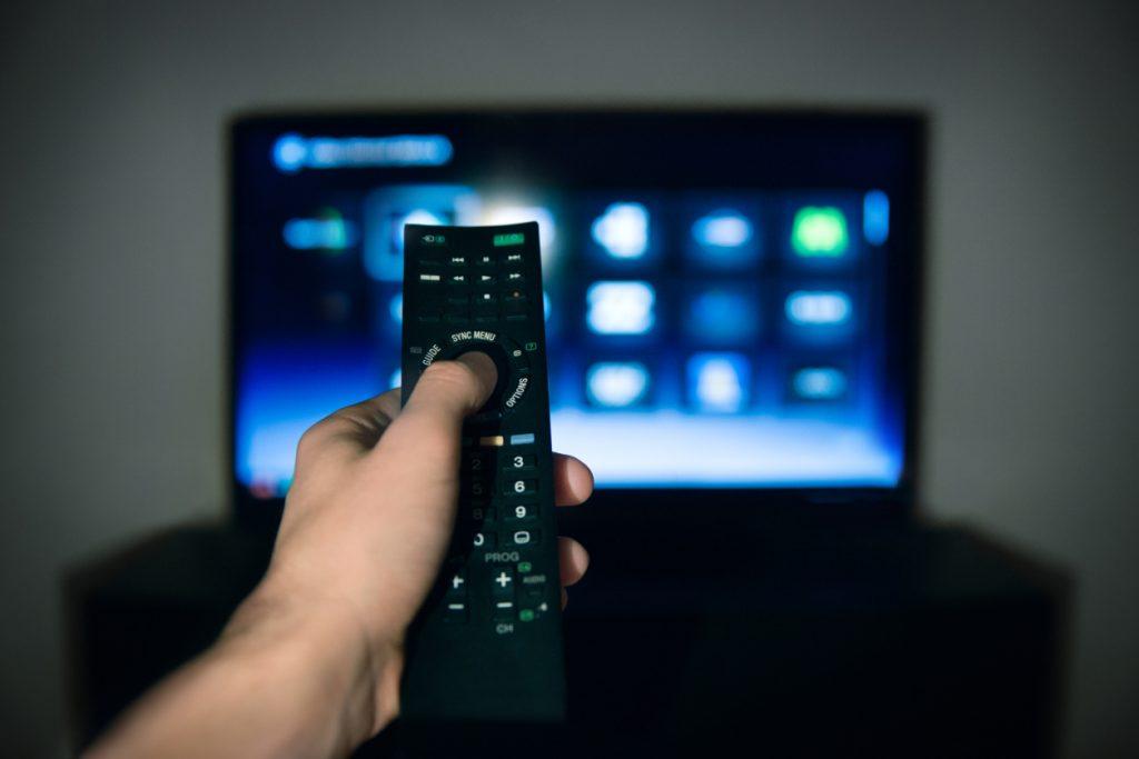 Male hand using Tv remote control